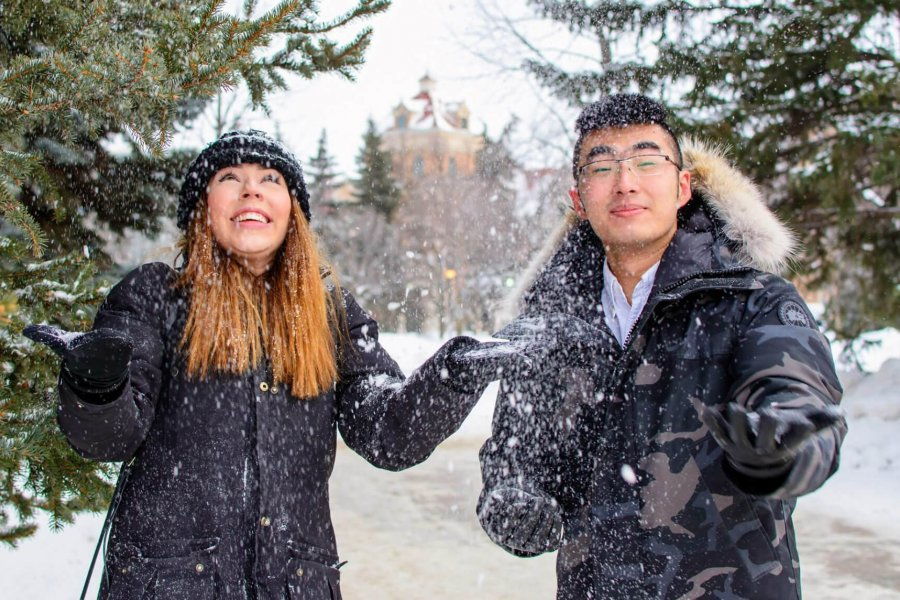 A student mentee and mentor stand together outside on a winter day smiling and playfully tossing snow in the air.