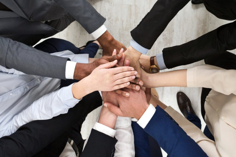 A diverse group of people stand together forming a circle and stack their hands on one another in the middle.