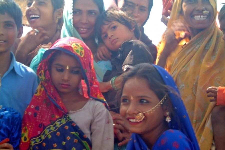 Colourfully dressed, smiling women and children from a community in India.