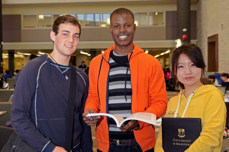 Three international students stand together in a library.