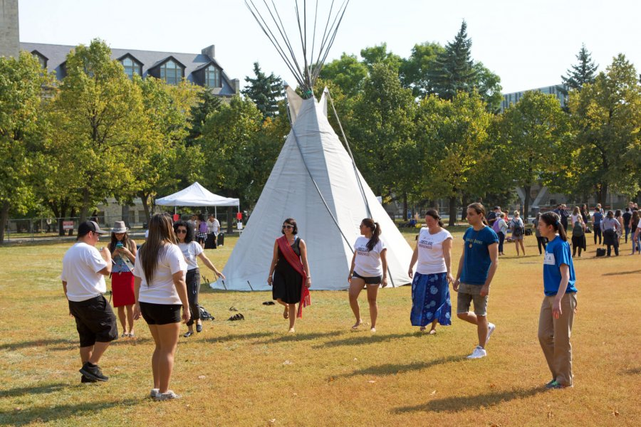 A group of indigenous students stand in front of a tepee and form a circle while  participating in an orientation activity.