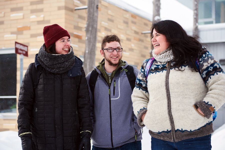 Three indigenous students walk together on campus on a snowy day.