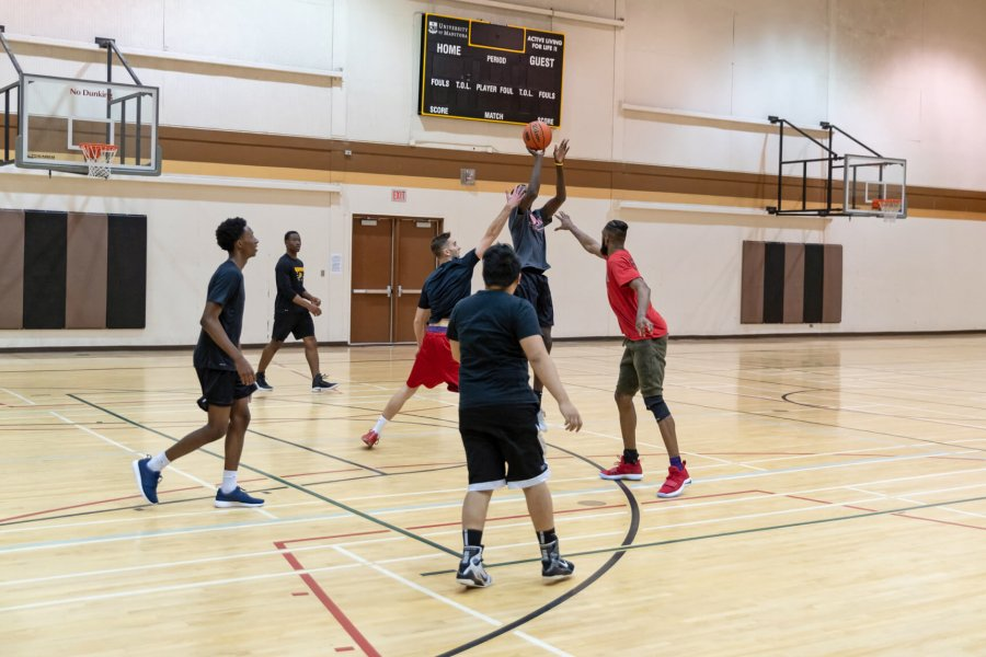 A group of 6 students playing a recreational basketball game on the Frank Kennedy Centre gymnasium basketball court.