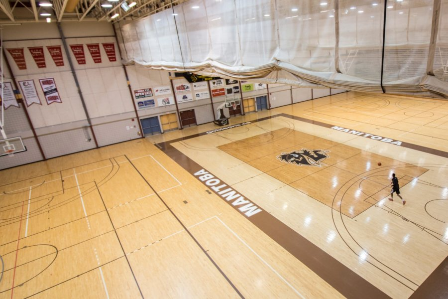 A student dribbles a basketball across the Investors Group Athletic Centre gymnasium basketball court.