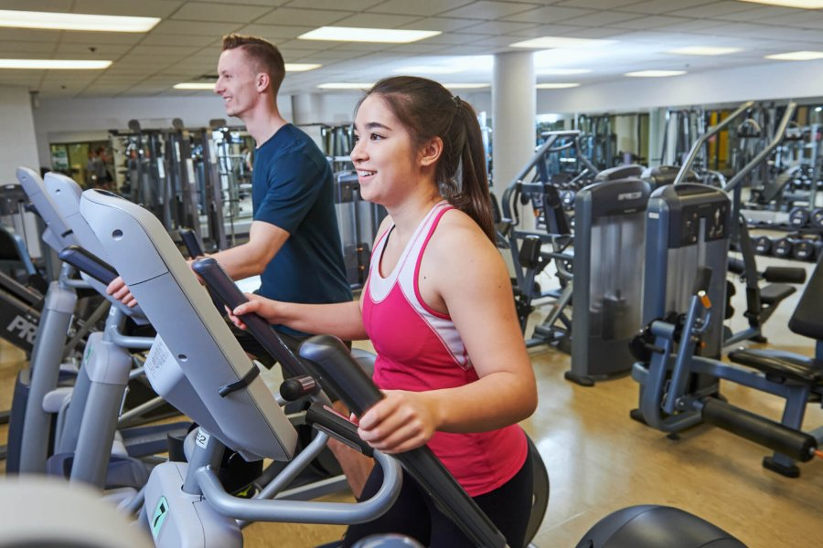 A man and woman getting a workout using the cardiovascular equipment at the Joe Doupe Recreation Centre.