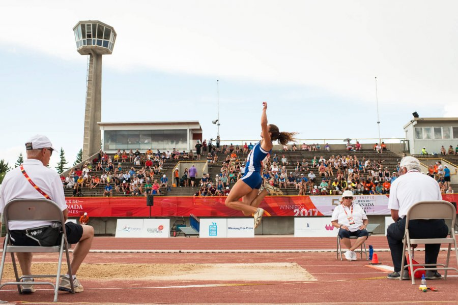 A competing long jump athlete caught mid air over the sand pit while a crowd of spectators watch from the University Stadium stands.