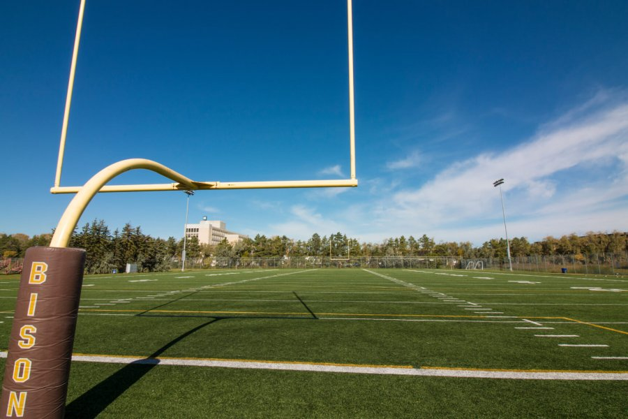 A view of the football sports field from the end zone goal posts.