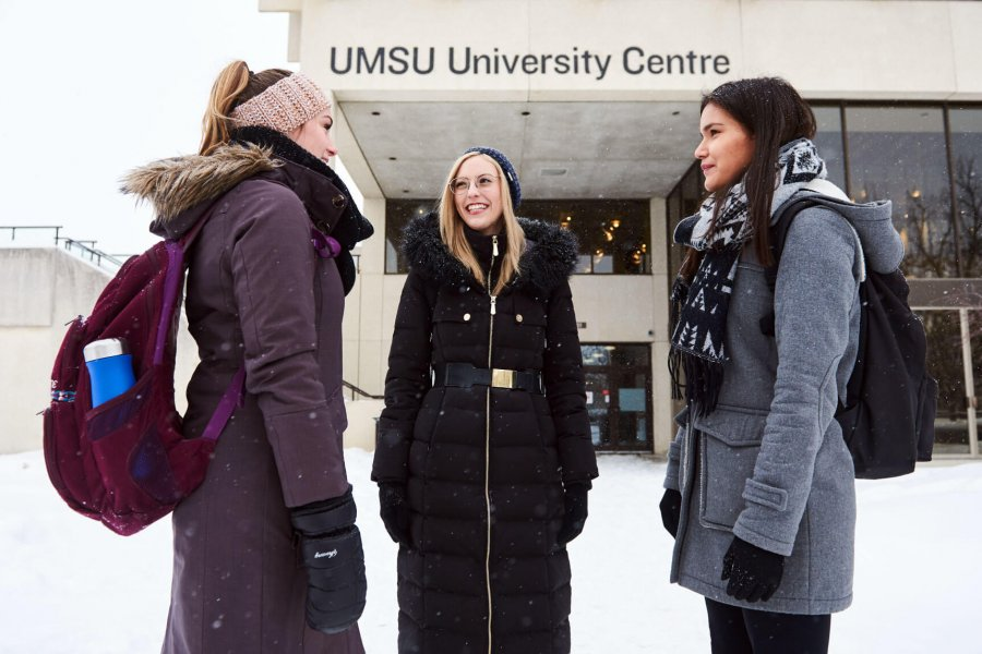 Three young women stand together outside of the UMSU University Centre building.
