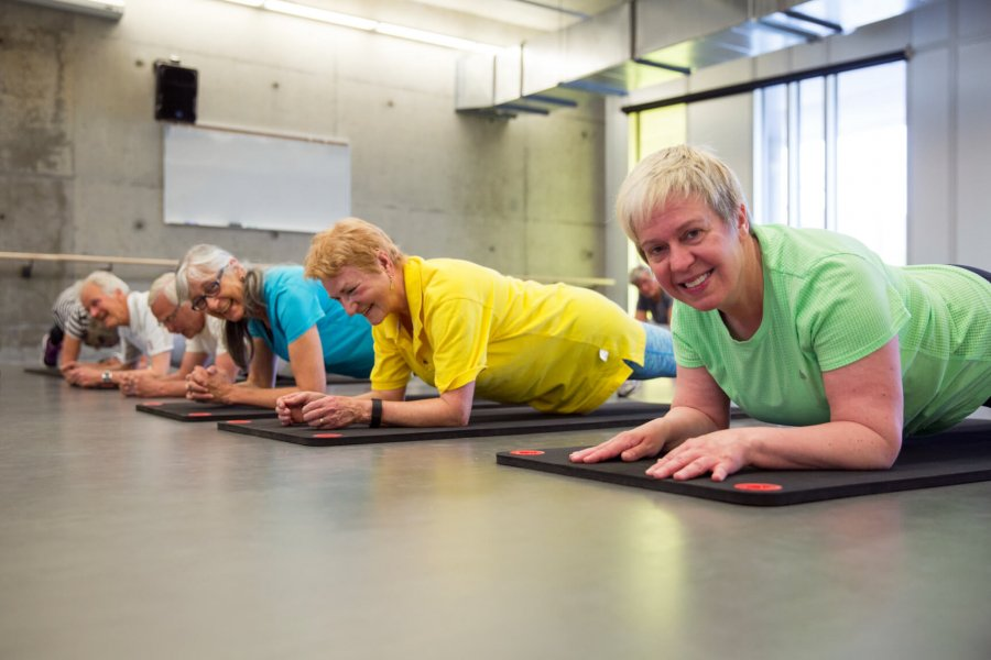 Senior Active living centre members perform low planks while participating in a group Aging actively fitness class.