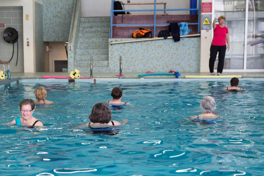 A group of adult swimmers in the pool following their group fitness instructors instructions.