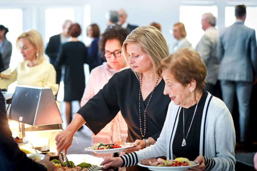 People help themselves to some food at a buffet line during an event.