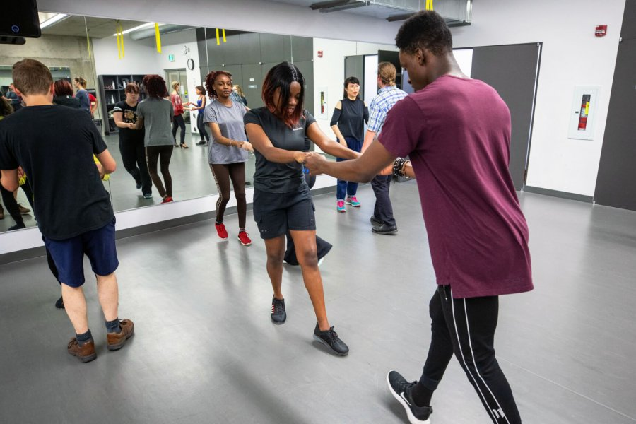 A room of people practicing dance with a partner.