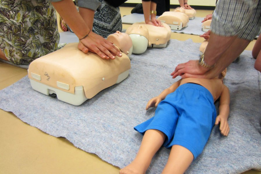 A class of six people learning how to perform CPR cardiopulmonary resuscitation on manikins.
