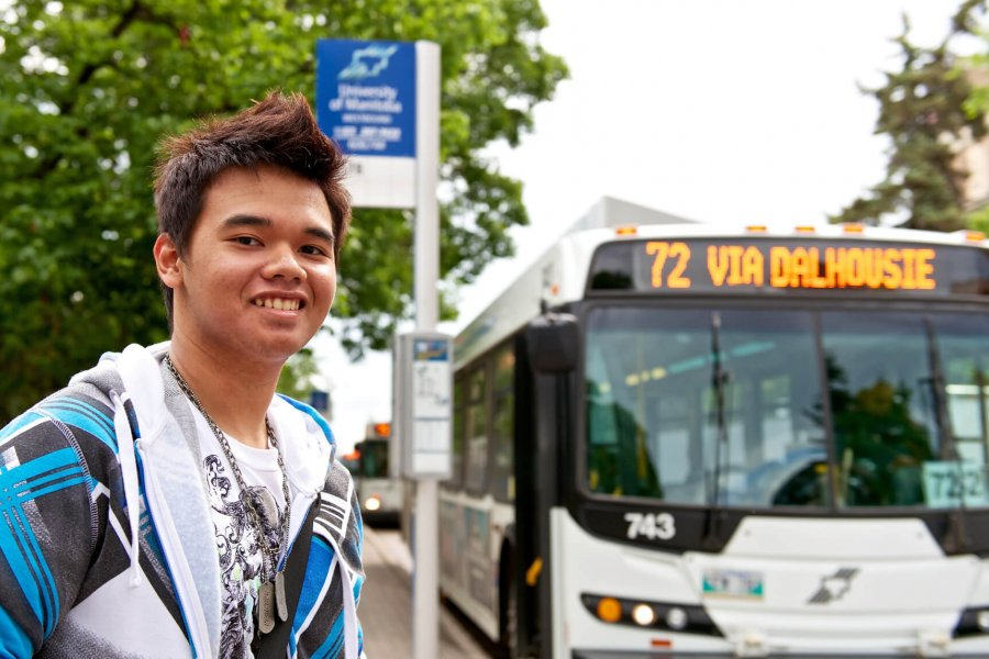 A University of Manitoba student stands at the bus stop waiting for the bus.