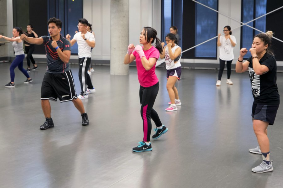 During a group fitness class members actively practice throwing jabs.