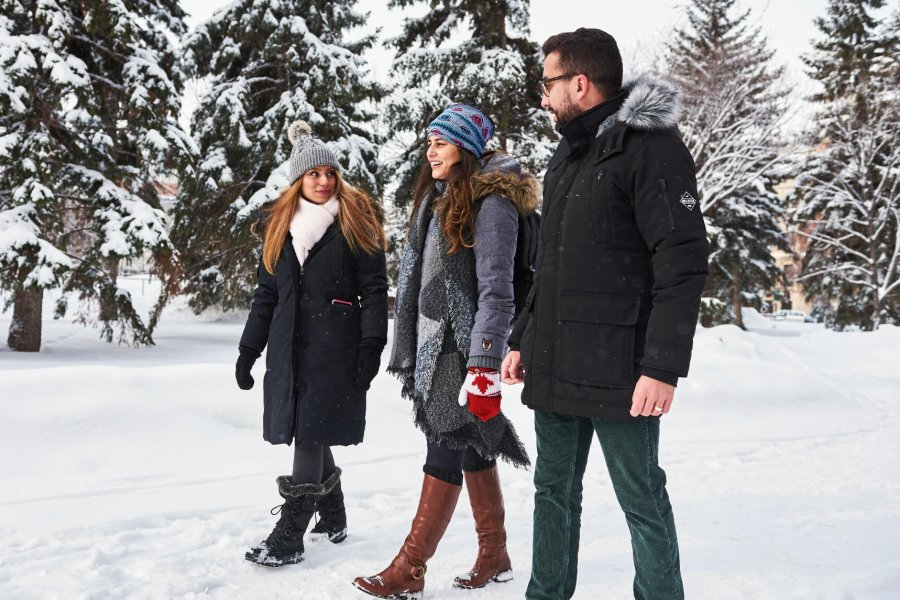 Three International students walk together outside on the University of Manitoba campus in winter.