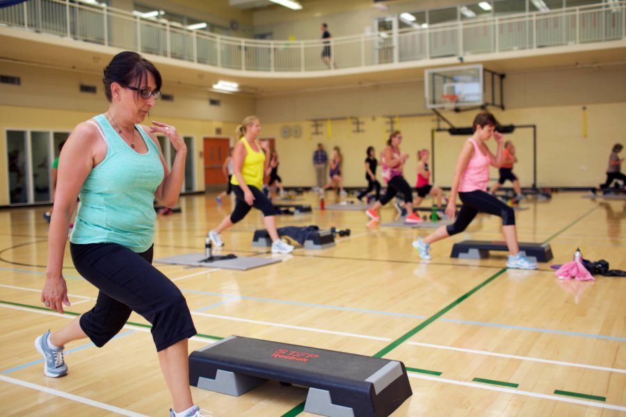 A group fitness instructor leads members in a group fitness class in a Joe Doupe gymnasium.