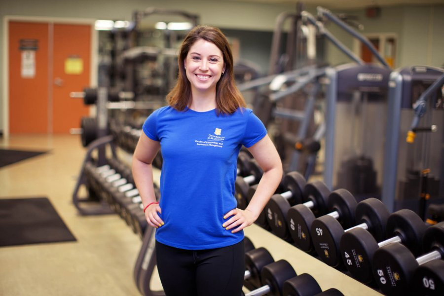 A Joe Doupe recreation centre personal trainer smiles while standing in front of a row of dumbbells.