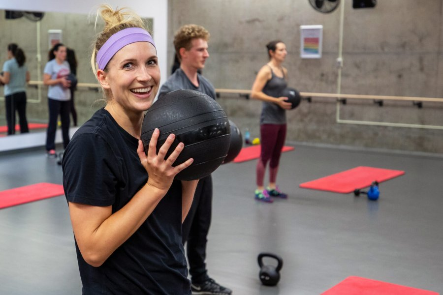 An Active Living Centre member smiles at the camera while holding a medicine ball during a group fitness class.