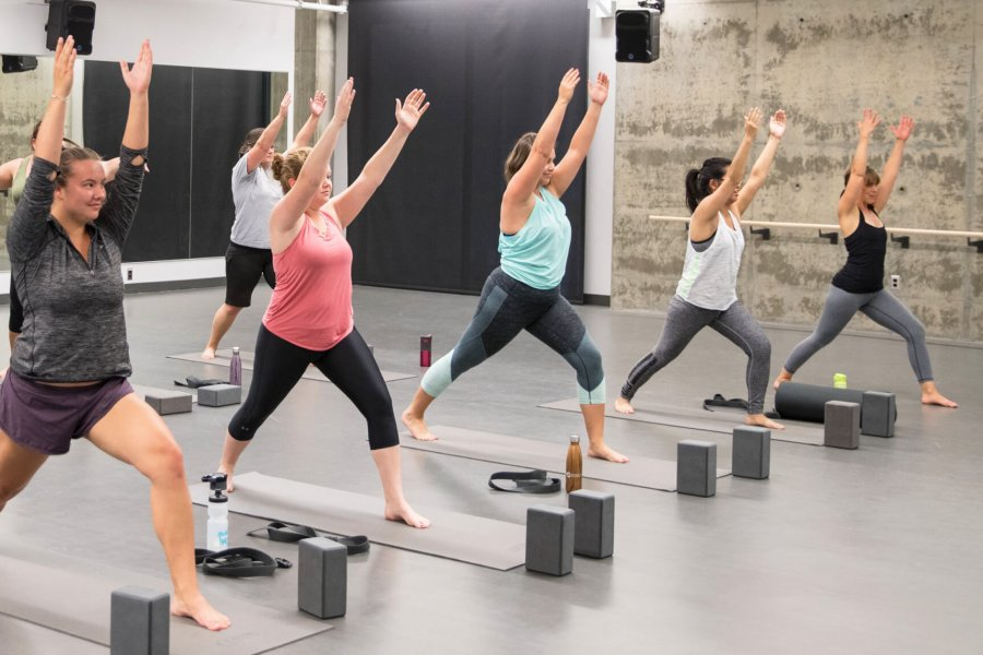 A group of people participating in a group fitness yoga class lunging with their arms held high in the air.