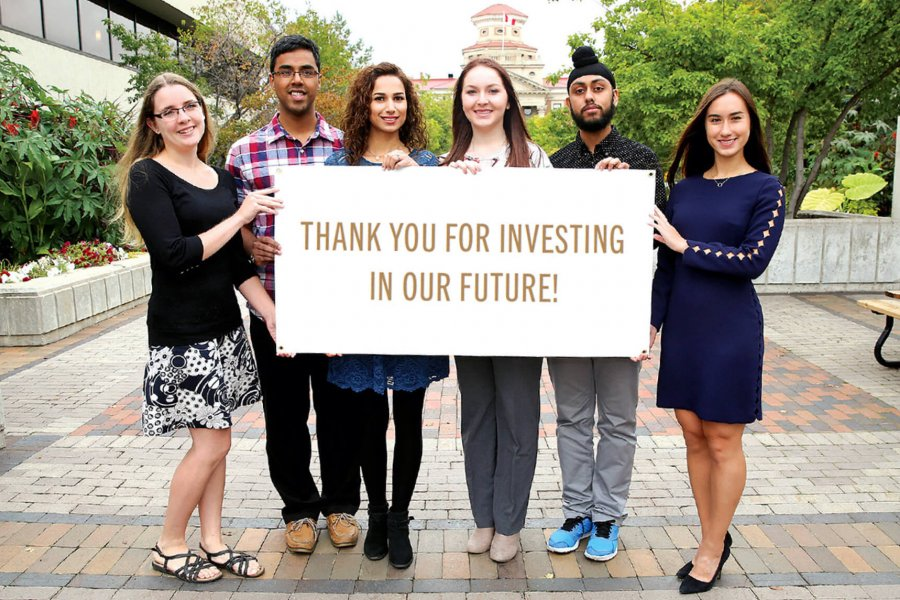 Six students stand together holding a sign that says thank you for investing in our future.