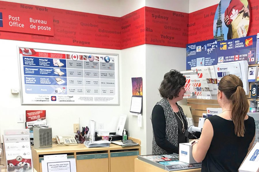 An employee of the University of Manitoba postal outlet assists a customer.