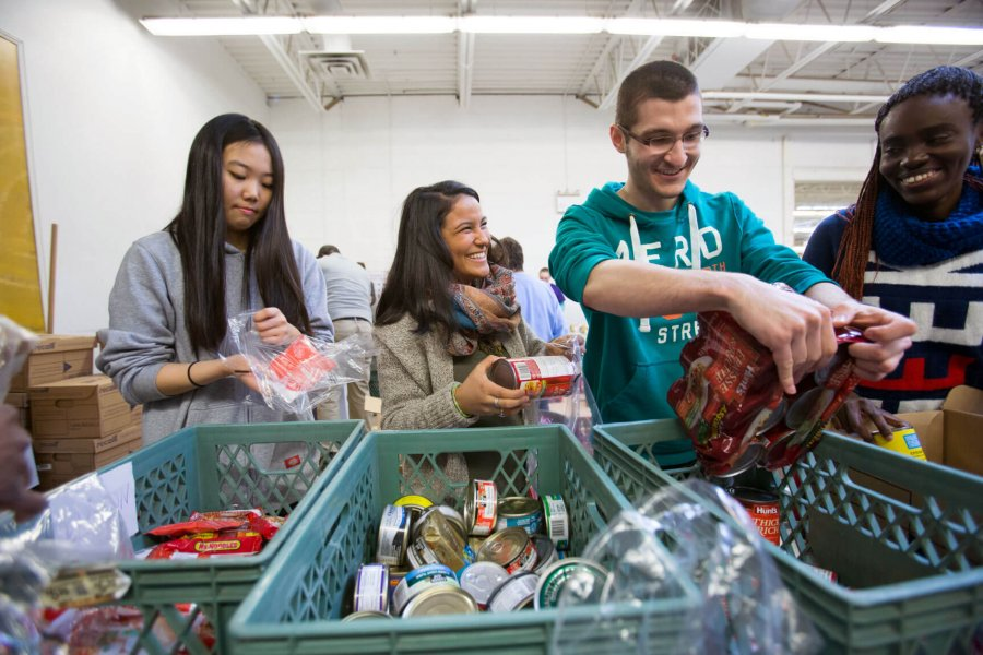 Four students pack non-perishable food items into bags at Winnipeg Harvest.