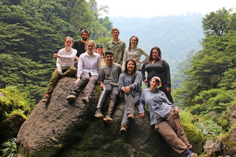 A group of students sit together on a large rock in the Amazon rainforest.