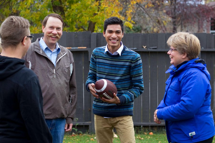 An international student stands in a backyard holding a football with his homestay family.