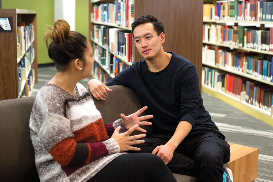 Two students sitting in a library together talking.