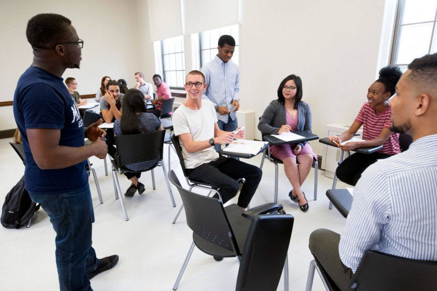 Students seated in circles receive instruction during a graduate student workshop.