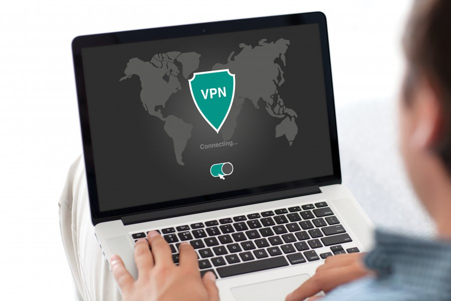 Man working on a laptop with a world map shown on and an shield symbol overlaid with VPN written across
