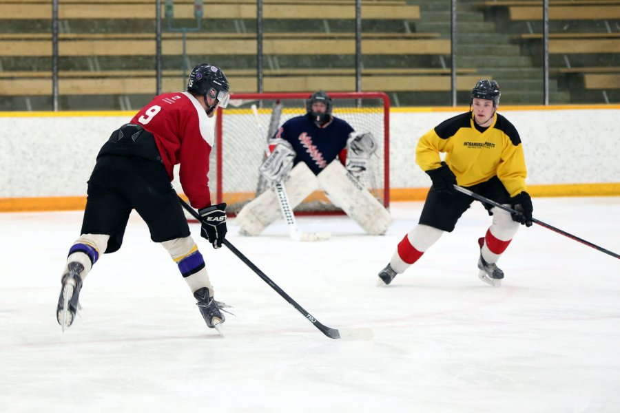 Three young adults playing a casual game of hockey.