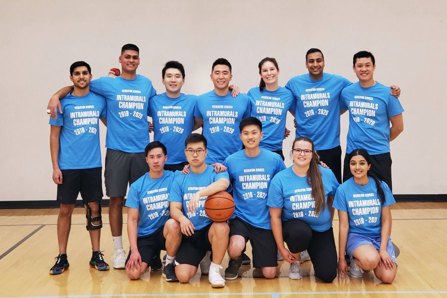 An intramural basketball champion team huddles together for a group photo.