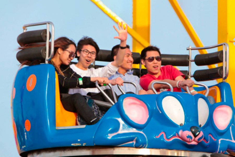 Four students smiling as they enjoy a carnival ride.