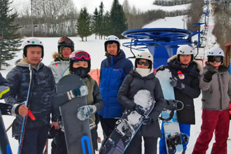 7 students stand together at a ski hill holding snowboards.