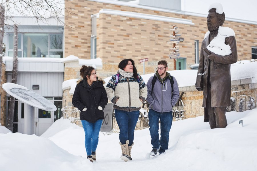 Three indigenous students walking together in front of the Migizii Agamik - Bald Eagle Lodge.