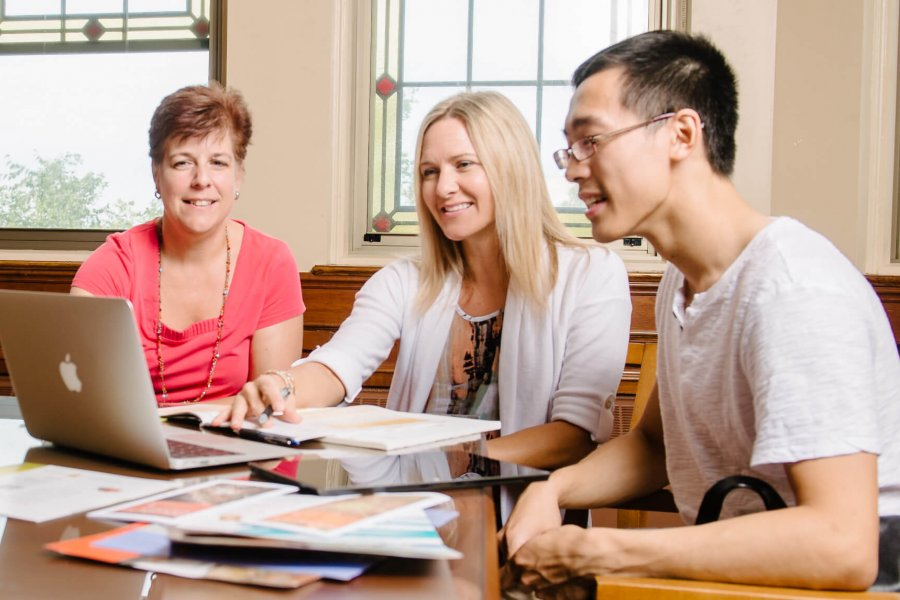 A first year student reviews his next steps with two advisors.
