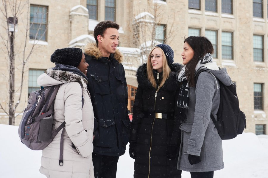 A group of 4 students dressed for the winter weather gather together in front of the Buller Science building.