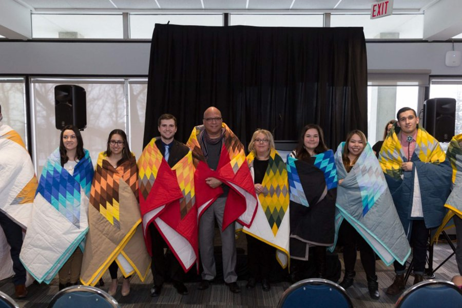 Recipients of the Indigenous Awards of Excellence in a group photo, wrapped in colourful star blankets.