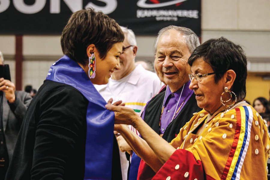 An indigenous student receives her sash at the Graduation Pow Wow.