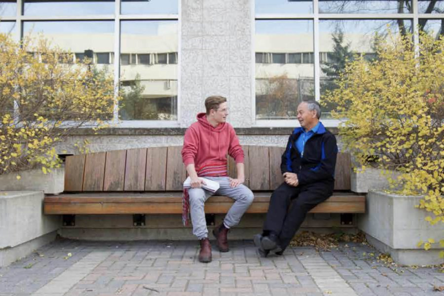 A Metis student sits on a bench and talks with Elder-in-Residence Norman Meade.
