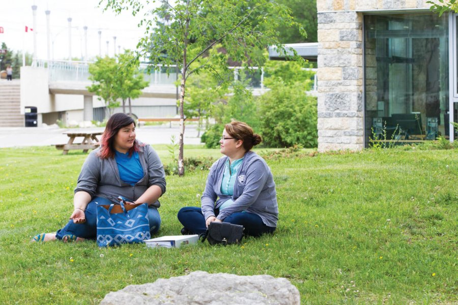 Two indigenous students sit together in a grassy area outside of  Migizii Agamik – Bald Eagle Lodge.