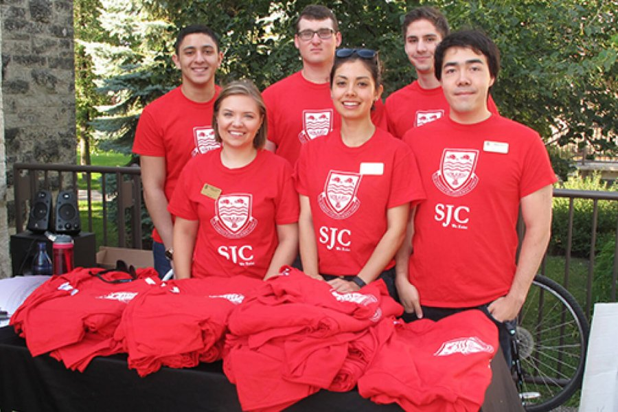 A group of six St. Johns College student residents stand together at a table wearing coordinating red St. Johns College t-shirts.