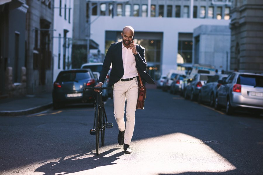 man walking with his bike while talking on mobile phone