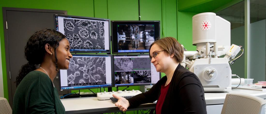 Two researchers sitting together in front of four large monitors in a lab talking.