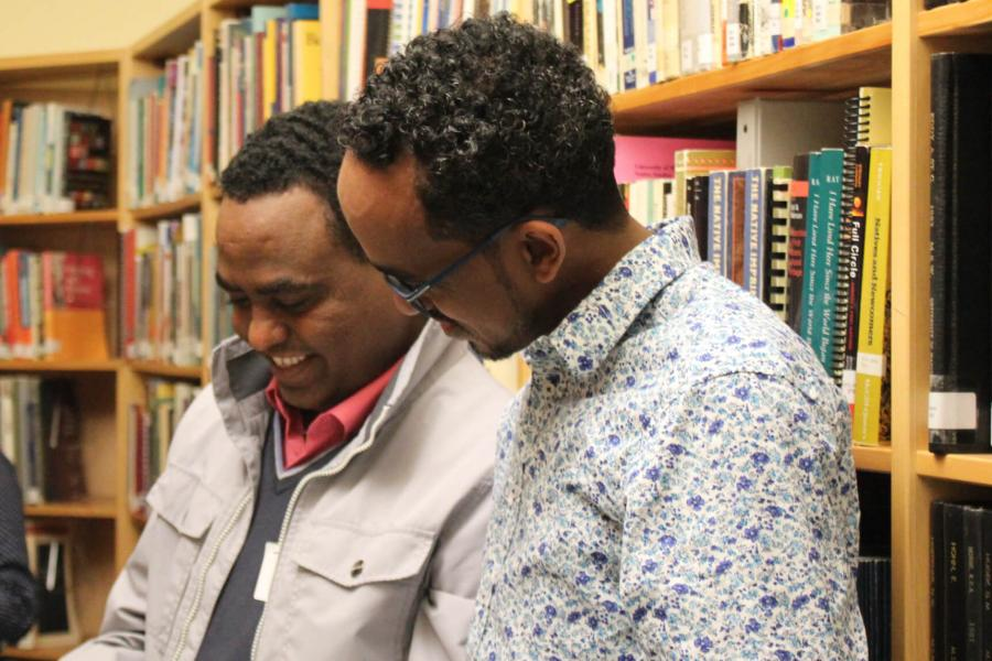 Two social work students talking in a library.