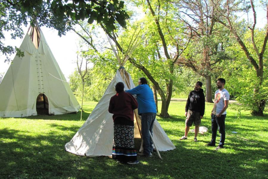 Indigenous knowledge keepers demonstrating how to construct a teepee.