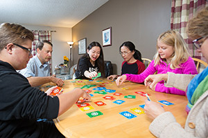 Homestay students play board games with their host family