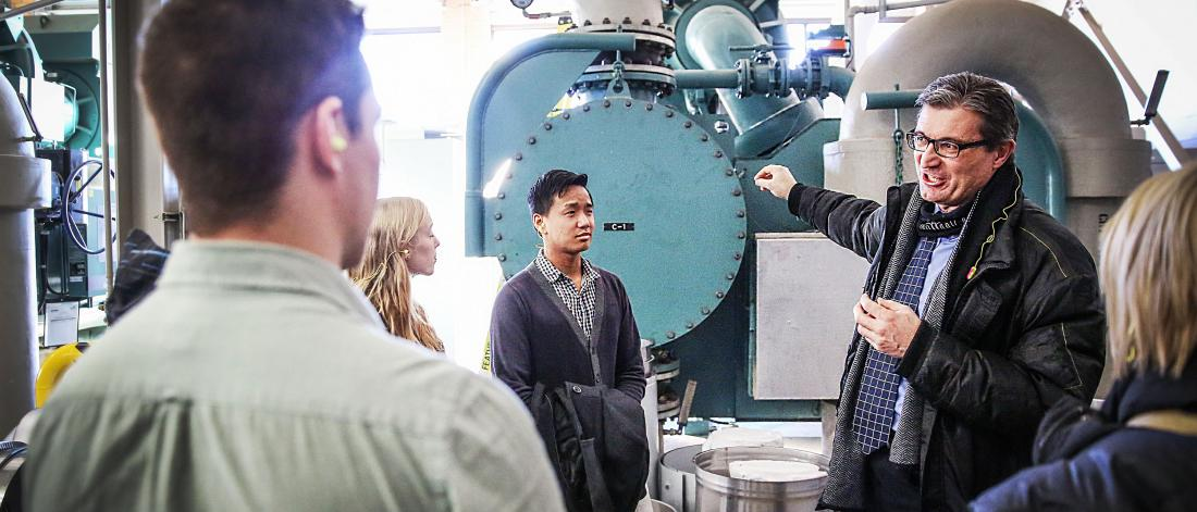 The university engineer showing students the inside of the UM powerhouse